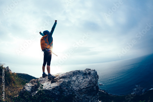 Fotografía Successful hiker outstretched arms at seaside mountain top cliff edge