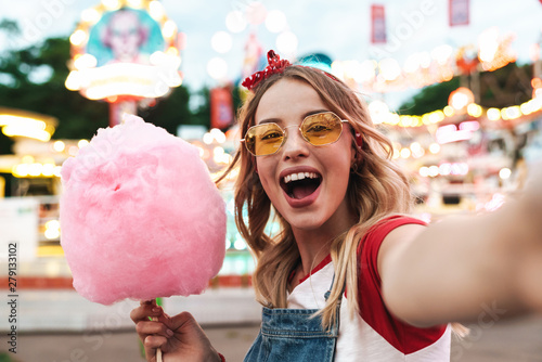 Canvas Image of excited blonde woman holding sweet cotton candy while taking selfie pho