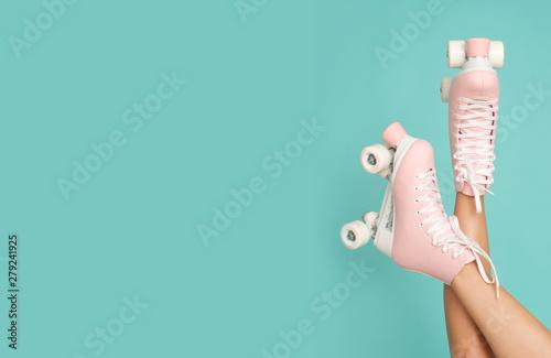 Fototapeta Legs up! Roller skates on slim leg isolated on the colorful background