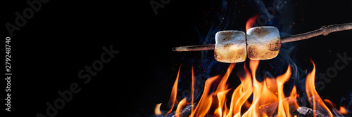 Fotografija Banner Of Two Marshmallows On A Stick Roasting Over Campfire On Black Background