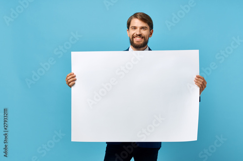 Wallpaper Mural man holding a white blank on a blue background