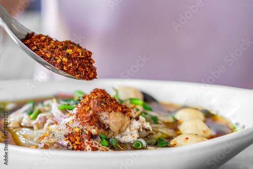 Obraz na płótnie Asian woman hand pouring chili powder on noodle bowl , unhealthy eating spicy fo