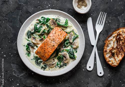 Tablou Canvas Baked salmon with creamy spinach mushrooms sauce on a dark background, top view