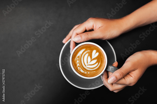 Canvas-taulu Cup of fresh cappuccino in woman hands on dark black metal table background