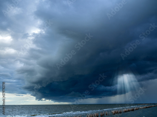 Obraz na plátně Sun beam in dark clouds and sky before thunderstorm at the seashore, Monsoon sea