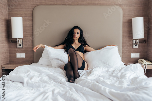 Canvas-taulu front view of sexy brunette girl in black stockings and underwear lying in bed