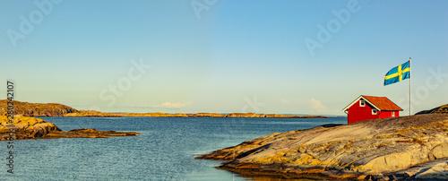 Leinwand Poster Rotes Haus in Schweden an der Schärenküste mit Flagge