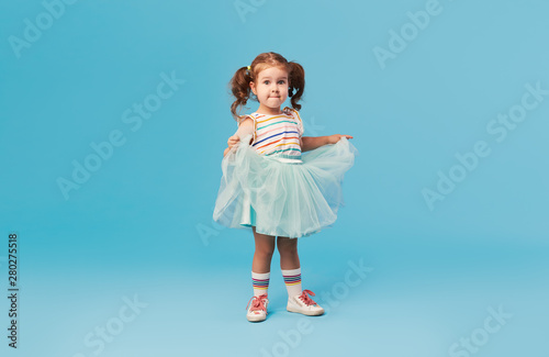 Canvas Print Little happy toddler child girl dreams of becoming ballerina in a cyan tutu skirt