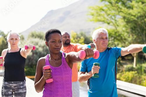 Obraz na plátně Mature fitness people exercising with dumbbells