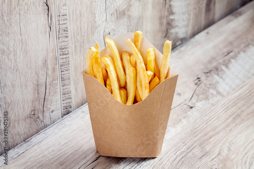 Photo Close up view on Potatoes French Fries in Carton Package Box Isolated on wooden background