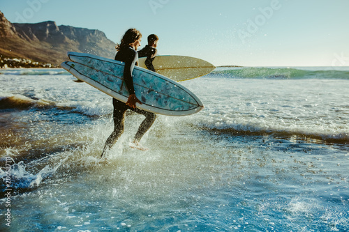 Fotografia To young surfers going for water surfing