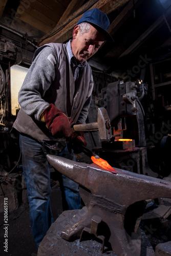 Fotografia blacksmith manually forging the molten metal