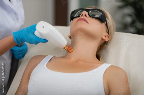 Obraz na plátně Blond woman getting her laser neck skin treatment.