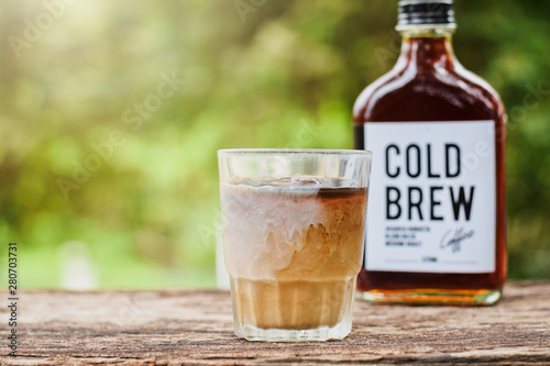 Foto Cold brew coffee with milk on a table outside with cold-brew coffee in a glass b