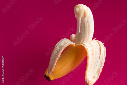 banana and drops of condensed milk on a vivid pink background Fototapete