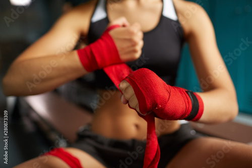 Obraz na plátne Close up of tough young woman putting on red hand wraps preparing for boxing pra