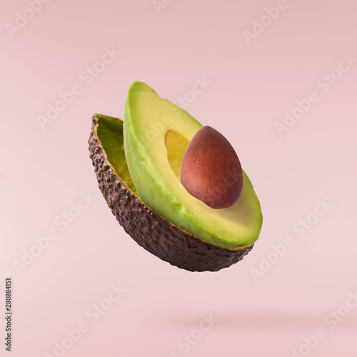 Fotografía Fresh ripe avocado with leaves falling in the air.