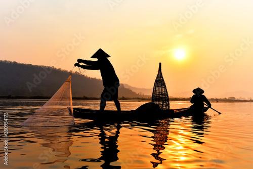 Canvas-taulu Asia fisherman net using on wooden boat casting net sunset or sunrise in the Mek