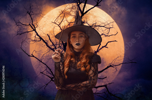 Fototapeta Halloween witch holding magic wand standing over dead tree, full moon and spooky