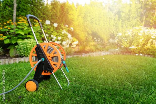 Fotografia garden hose reel on green lawn in backyard copy space