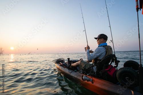 Obraz na płótnie Young Man Kayak Fishing at Sunrise in Canada