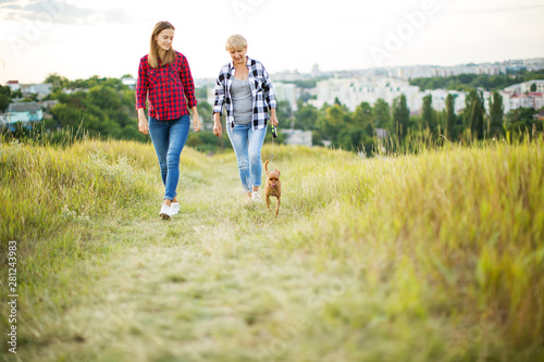 Fotografia Mother and adult daughter with dog outdoor in park.