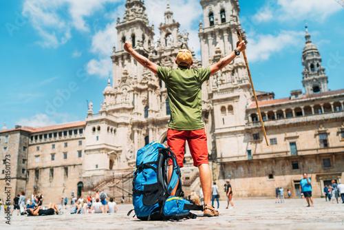 Carta da parati Young backpacker man pilgrim standing with raised arms on the Obradeiro square (plaza) - the main square in Santiago de Compostela as a end of his Camino de Santiago pilgrimage