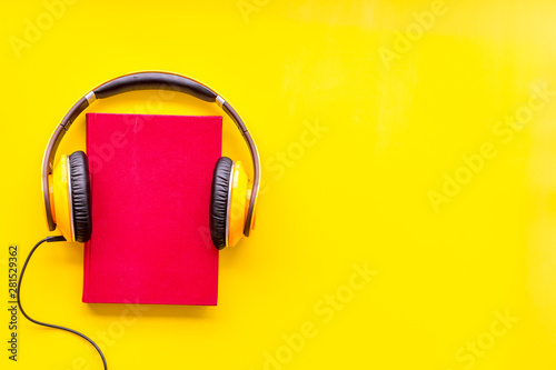 Wallpaper Mural listen to audio books with headphone on yellow background flatlay mock up