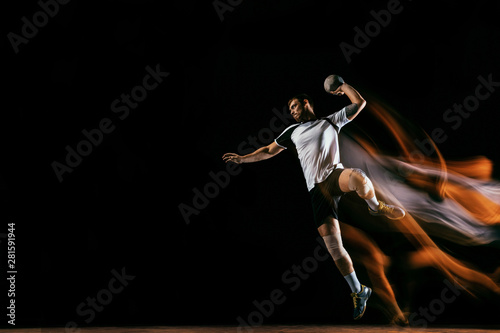 Fototapeta Caucasian young handball player in action and motion in mixed lights over black studio background