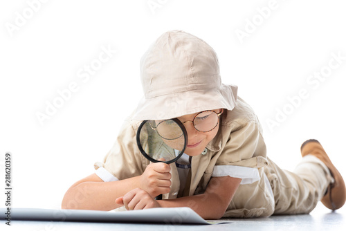 Obraz na płótnie focused explorer child in hat and glasses looking at placard through magnifying