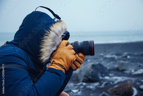 Fotografía Photographer Takes picture on black sands beach with winter clothes