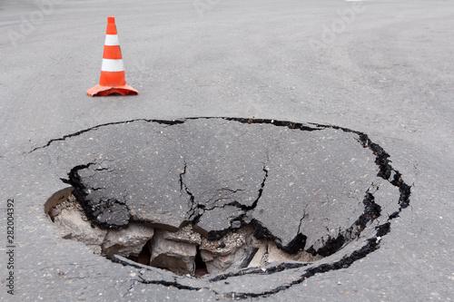 Obraz na plátně Deep sinkhole on a street city and orange traffic cone
