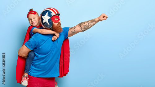 Fotografia Indoor shot of powerful dad in protective helmet carries small child on back, play superhero game, fly together and make good things for people, isolated on blue background