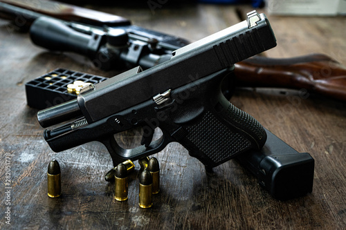 Foto Guns and ammunition on the wooden table, top view and free space for entering your text