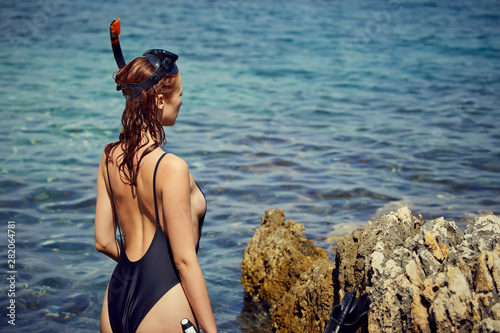 Stampa su Tela sexy woman with fins and crossbow is preparing to hunt for fish