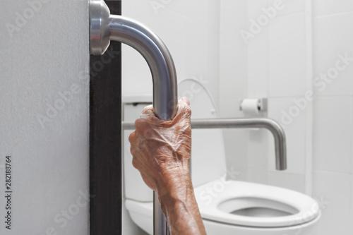 Canvas Print Elderly woman holding on handrail in bathroom