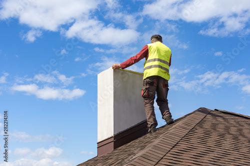 Obraz na płótnie Man measuring chimney on roof top of new house under construction