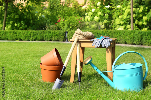 Wallpaper Mural Set of gardening tools and stool on green grass