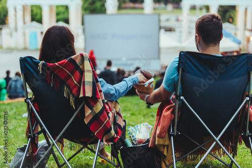 Slika na platnu couple sitting in camp-chairs in city park looking movie outdoors at open air ci