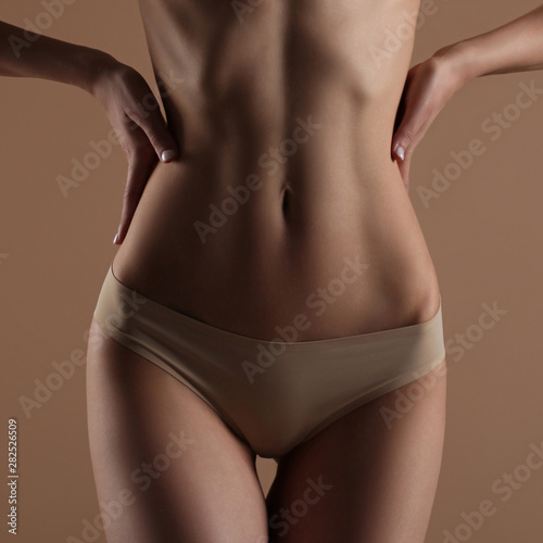 Skinny young woman in lingerie holds her hands on her waist