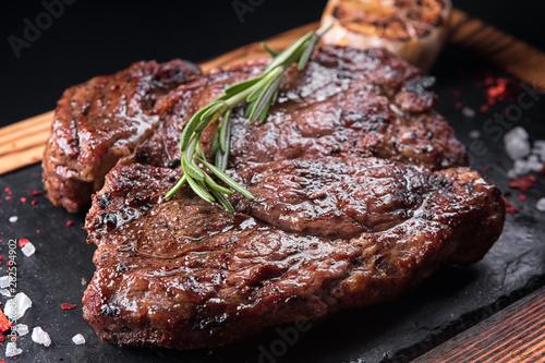 Fotografija Fried meat steak on slate on a black background