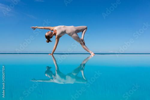 Fotografia Beautiful young woman yoga instructor doing Wild Thing (Camatkarasana) asana on the edge of the pool enjoying warm morning sun while relaxing in a sunny country