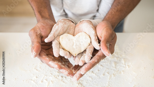 Photo Afro man hands holding child hands with heart shaped pastry