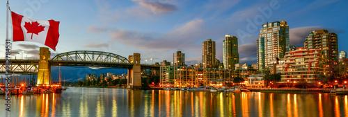 Fototapeta premium Kanadyjska flaga przed widokiem Wyspa Granville w pobliżu Burrard Street Bridge o zmierzchu w Vancouver, Kanada