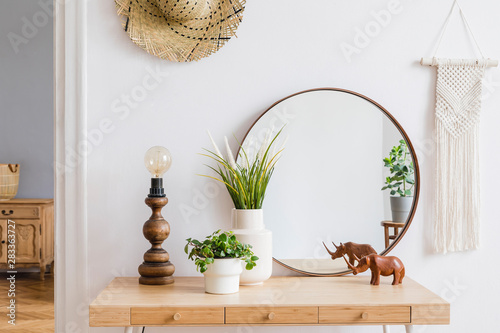 Valokuva Sunny boho interiors of apartment with  mirror, dressing table, table lamp, flowers, plants, rattan hat, sculpture, macrame and design accessories