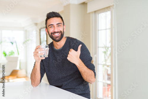 Fotografía Handsome hispanic man drinking a fresh glass of water happy with big smile doing