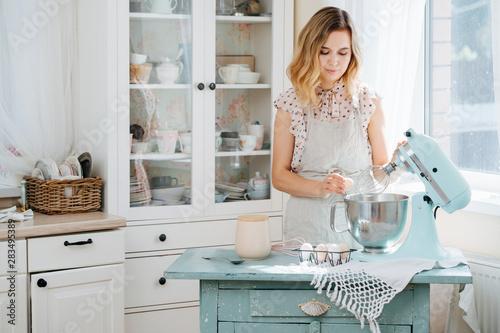 Obraz na płótnie young woman using a food processor to make a dough