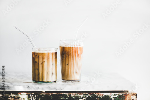 Stampa su Tela Homemade iced latte coffee in glasses with straws on grey marble table, white wall at background, copy space