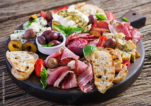 Fotografia Antipasto platter with ham, prosciutto, salami, blue cheese, mozzarella with pesto and olives on a wooden background