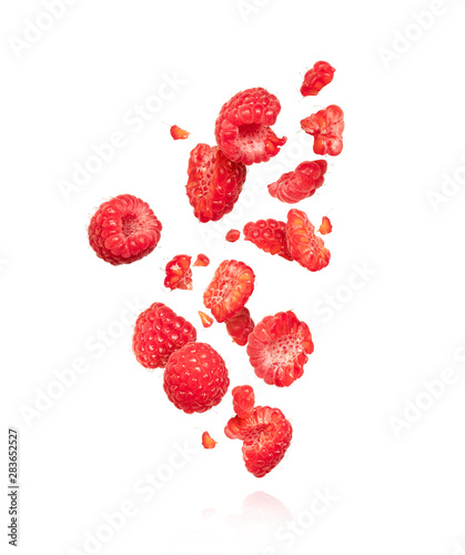 Fotografia Whole and sliced raspberries in the air, isolated on a white background